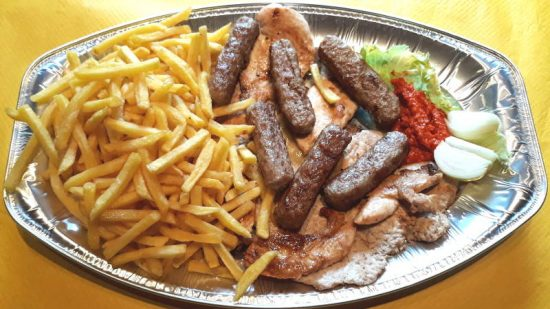 Mixed grilled meat with french fries, onion and ajvar.